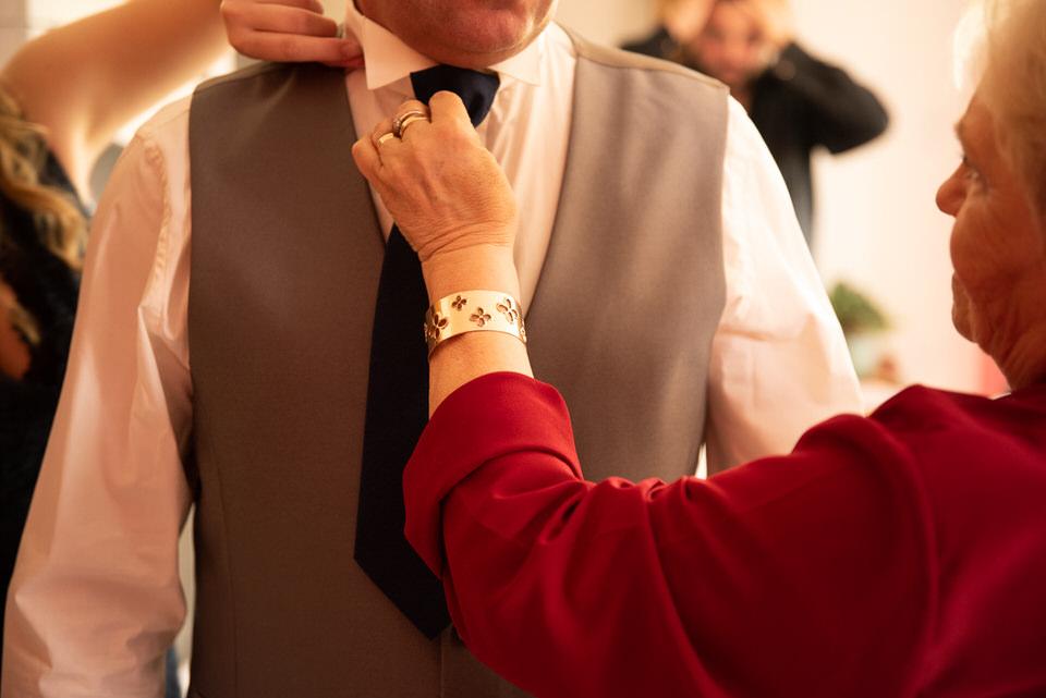 femme ajustant cravate du marié