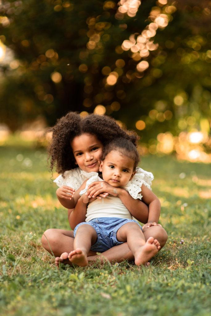 deux enfants se tenant dans les bras assises par terre