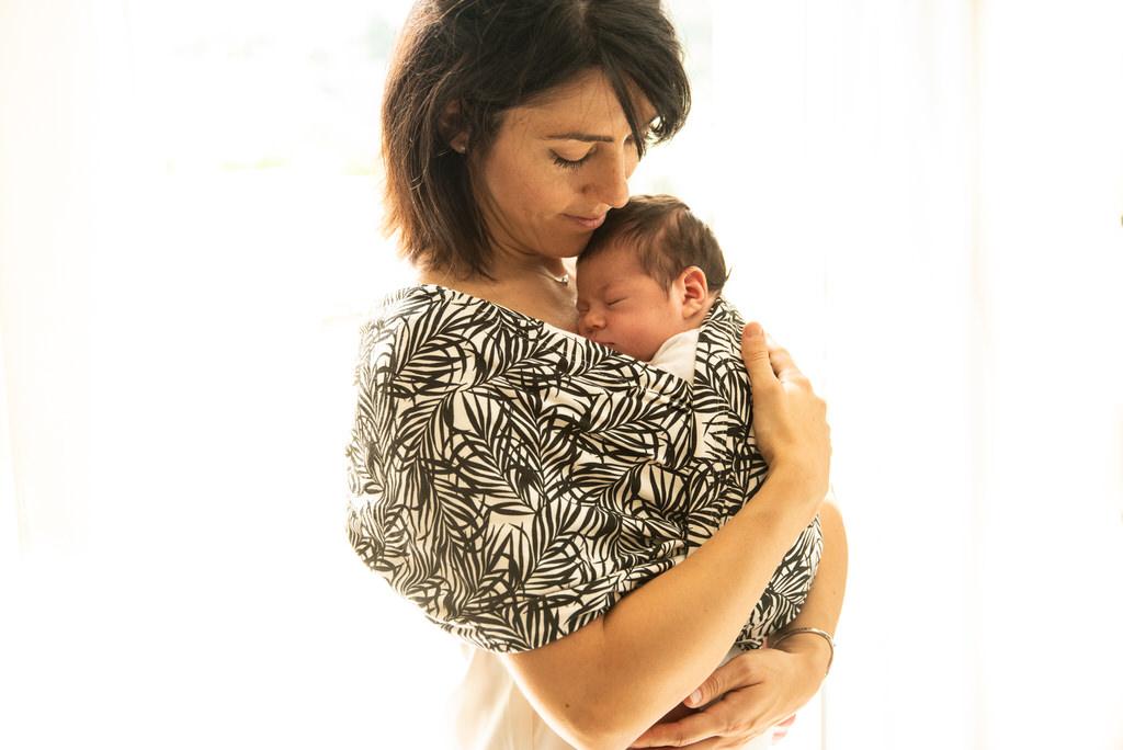 Image représentant une maman berçant son bébé dans en portage